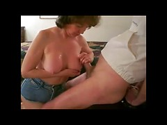 Mature lady plays with her husbands cock - she strokes it and fucks it with her big breasts